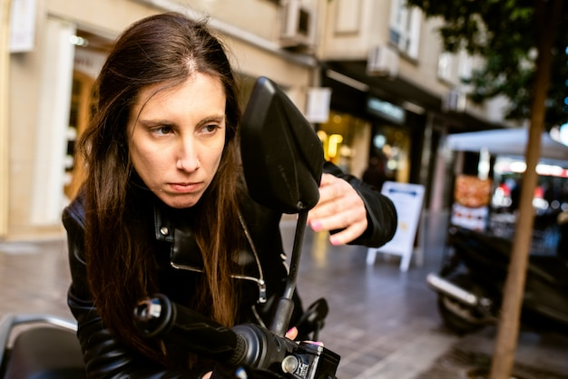 Une jeune entrepreneure inquiète de son apparence juste avant une réunion importante, en se maquillant dans la rue.