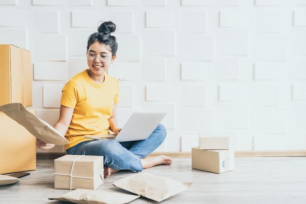 Jeune entreprise asiatique démarre le propriétaire du vendeur en ligne à l'aide d'un ordinateur pour vérifier les commandes des clients par e-mail ou site web et préparer des colis