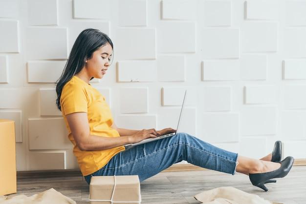 Jeune entreprise asiatique démarrer le propriétaire du vendeur en ligne à l'aide d'un ordinateur pour vérifier les commandes des clients par e-mail ou site web et préparer les colis