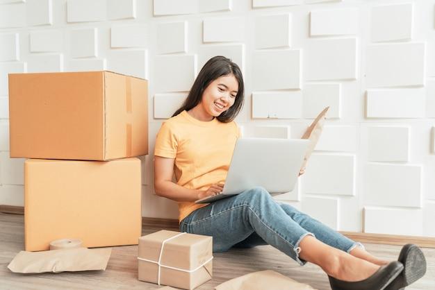 Jeune entreprise asiatique démarrer le propriétaire du vendeur en ligne à l'aide d'un ordinateur pour vérifier les commandes des clients par e-mail ou site web et préparer des colis