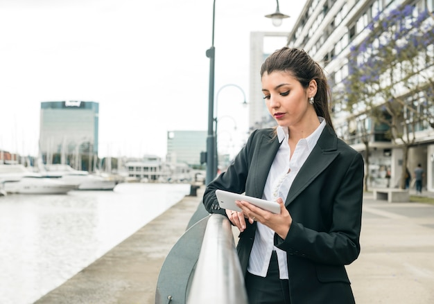 Jeune entreprise debout près de la rambarde touchant sur un téléphone intelligent à l'extérieur