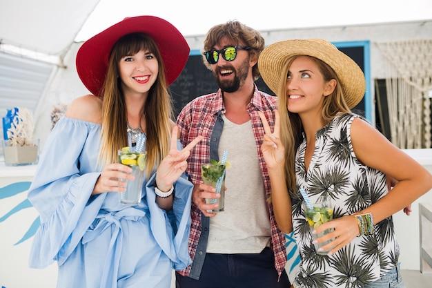 Jeune entreprise hipster d'amis en vacances au café d'été, boire des cocktails mojito, style positif heureux, sourire heureux, deux femmes et homme s'amusant ensemble, parler, flirter, romance, trois
