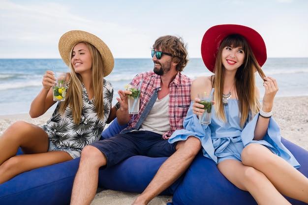 Jeune entreprise hipster d'amis en vacances au café de la plage, boire un cocktail mojito