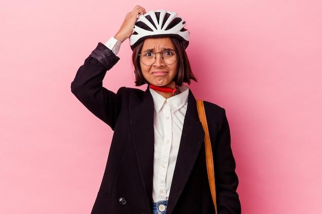 Jeune entreprise métisse femme portant un casque de vélo isolé sur un mur rose en état de choc, elle s'est souvenue d'une réunion importante