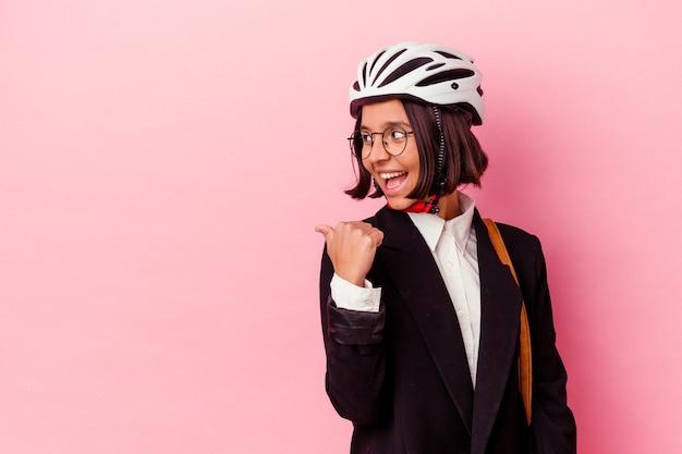 Jeune entreprise métisse femme portant un casque de vélo isolé sur des points de mur rose avec le pouce à l'écart, en riant et sans soucis