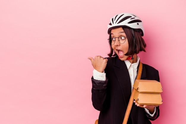 Jeune entreprise métisse femme portant un casque de vélo tenant un hamburger isolé sur des points de mur rose avec le pouce à l'écart, en riant et sans soucis