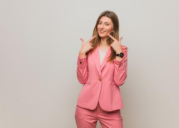Jeune entreprise russe fille sourit, pointant la bouche