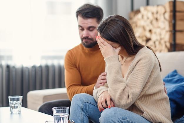 Jeune épouse aimante soutenant son mari déprimé pendant une séance de psychothérapie avec un conseiller, espace libre