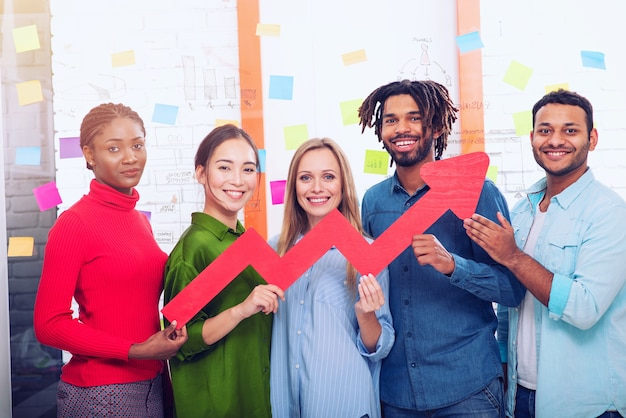 Jeune équipe commerciale heureuse et colorée tient une flèche statistique rouge. concept de croissance, de réussite et de profit
