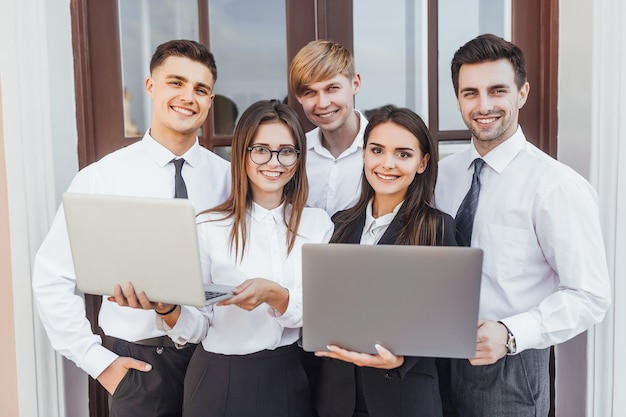 Jeune équipe commerciale prometteuse de filles et de garçons dans une image d'entreprise avec des ordinateurs portables dans leurs mains.