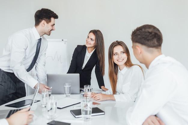 La jeune équipe commerciale prospère lors de la réunion sourit et discute des problèmes commerciaux dans une salle de conférence moderne