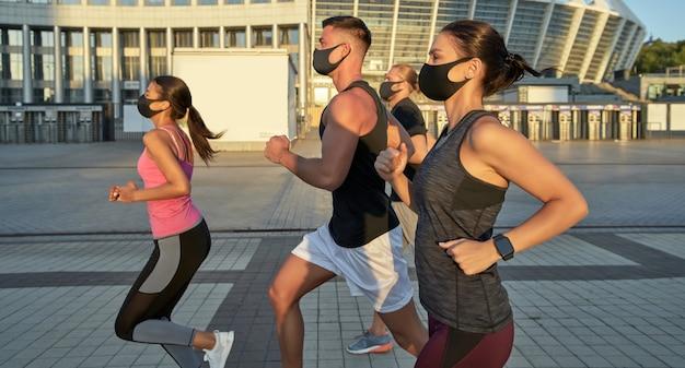Jeune équipe de course multi-courses en formation de masques de protection