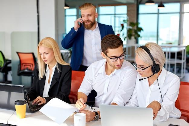 Une jeune équipe s'est concentrée sur le travail sur ordinateur portable tandis que le directeur près d'eux