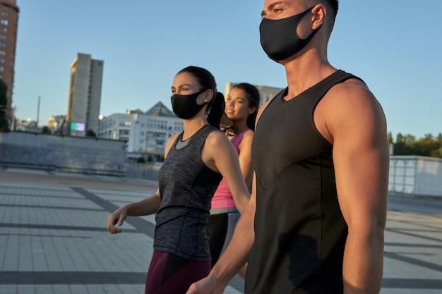 Jeune équipe sportive multi-courses dans des masques de protection en cours d'exécution