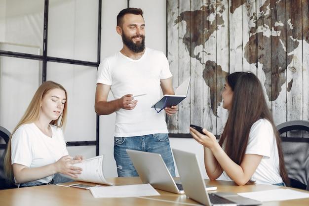 Jeune équipe travaillant ensemble et utilisant l'ordinateur portable