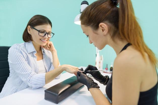 Jeune esthéticienne dans un salon de beauté des ongles faisant manucure