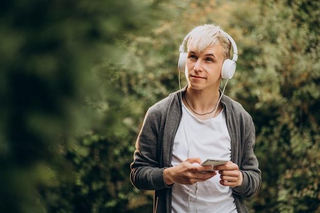 Jeune étudiant adulte dans les écouteurs dans le parc