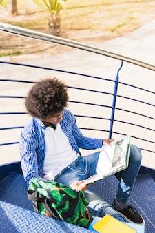 Jeune étudiant africain assis sur un escalier en lisant le livre