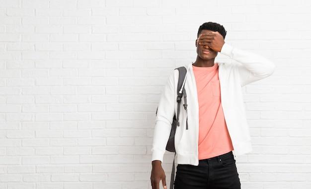 Jeune étudiant afro américain couvrant les yeux à la main. je ne veux pas voir quelque chose