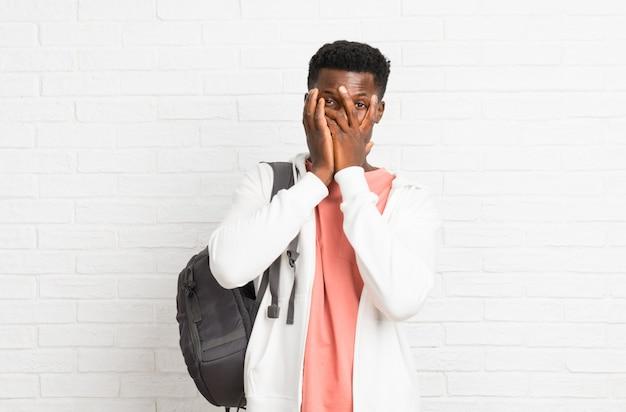 Jeune étudiant afro américain couvrant les yeux par les mains et regardant à travers les doigts