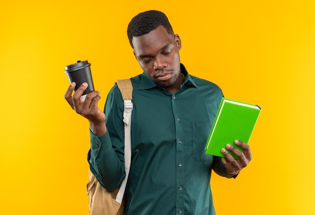 Jeune étudiant afro-américain endormi avec sac à dos tenant un livre et une tasse en papier
