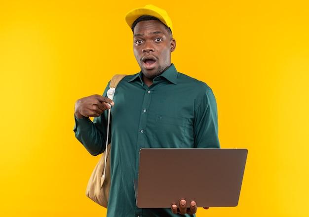 Jeune étudiant afro-américain surpris avec casquette et sac à dos tenant et pointant sur un ordinateur portable isolé sur un mur orange avec espace de copie