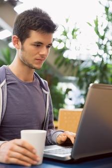 Jeune étudiant à l'aide de son ordinateur portable au café