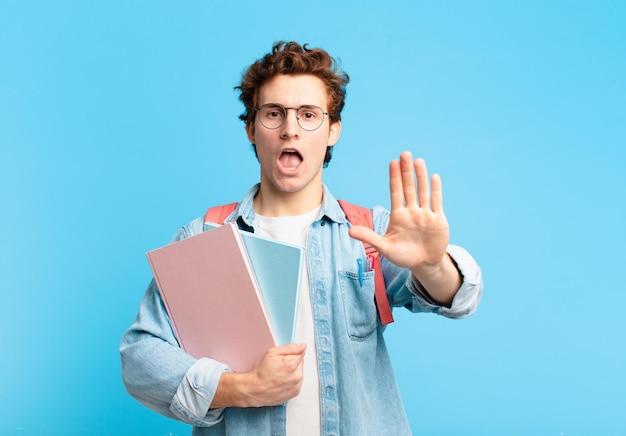 Jeune étudiant à l'air sérieux, sévère, mécontent et en colère montrant la paume ouverte faisant un geste d'arrêt