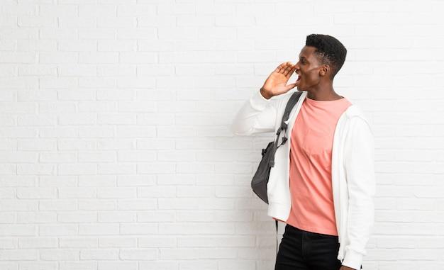 Jeune étudiant américain afro criant avec la bouche grande ouverte sur le côté
