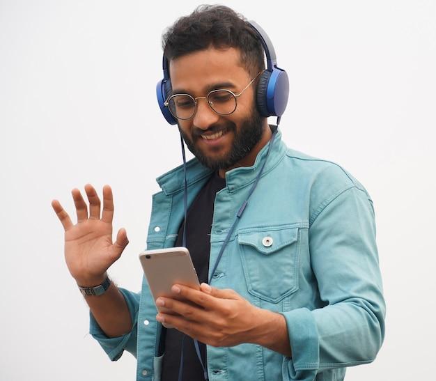 Un jeune étudiant en appel vidéo et casque en ligne education concept