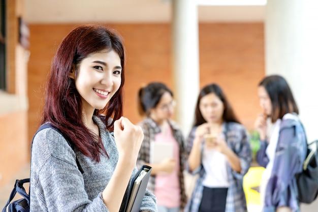 Jeune étudiant asiatique attrayant heureux souriant à la caméra