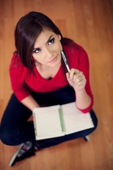 Jeune étudiant assis sur le sol