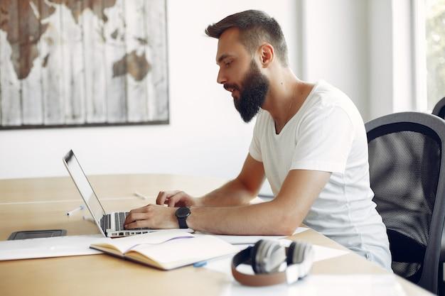 Jeune étudiant assis à la table et utilise son ordinateur portable