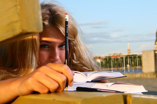 Jeune étudiant attrayant, lisant le livre