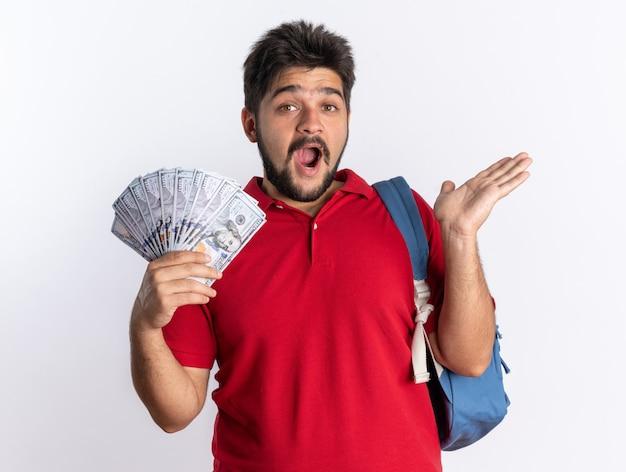 Jeune étudiant barbu en polo rouge avec sac à dos tenant de l'argent étonné et surpris debout sur un mur blanc