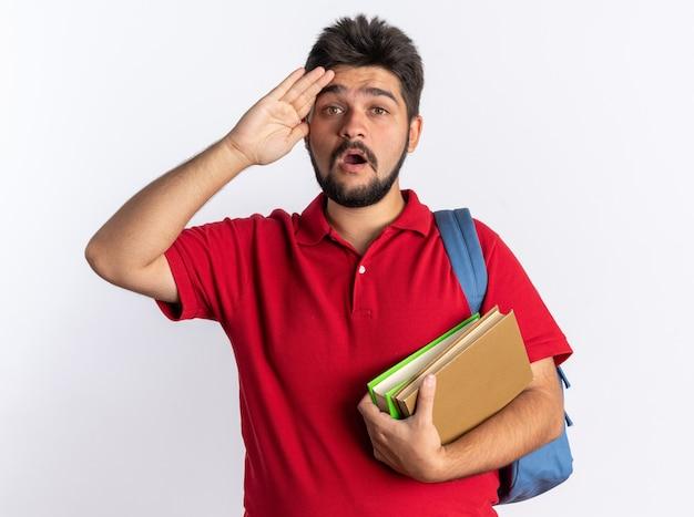 Jeune étudiant barbu en polo rouge avec sac à dos tenant des cahiers étonné et surpris debout sur un mur blanc