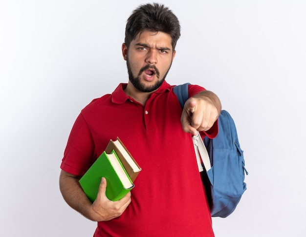 Jeune étudiant barbu en polo rouge avec sac à dos tenant des cahiers pointant avec l'index en colère et émotif debout sur un mur blanc