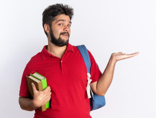 Jeune étudiant barbu en polo rouge avec sac à dos tenant des cahiers présentant un espace de copie avec le bras souriant joyeusement debout sur un mur blanc