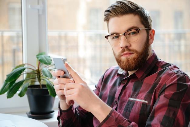 Jeune étudiant barbu portant des lunettes à l'aide de téléphone portable.