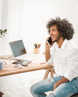 Jeune étudiant beau parler téléphone mobile alors qu'il était assis au bureau en bois avec ordinateur dessus