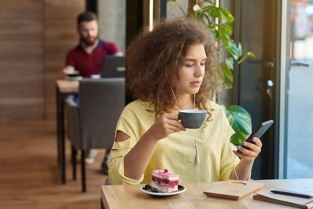 Jeune étudiant bouclé portant une blouse jaune, boire du café, à l'aide de smartphone.