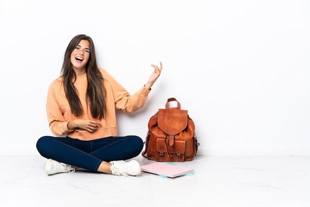 Jeune étudiant brésilien femme assise sur le sol faisant le geste de la guitare