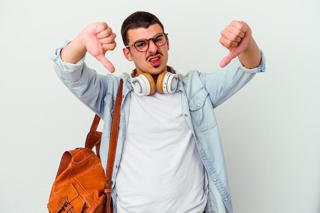 Jeune étudiant caucasien écoutant de la musique isolée sur blanc montrant le pouce vers le bas et exprimant son aversion.