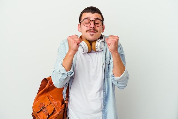 Jeune étudiant caucasien écoutant de la musique isolée sur un poing blanc, se sentant heureux et réussi. notion de victoire.