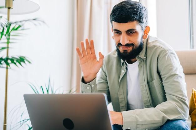 Jeune étudiant caucasien étudiant avec un ordinateur portable à distance à la maison à l'aide d'un appel vidéo, tissant. concept d'éducation à distance.