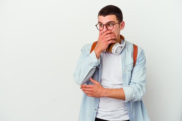 Jeune étudiant caucasien homme écoutant de la musique isolée sur un mur blanc réfléchie à la recherche d'un espace de copie couvrant la bouche avec la main