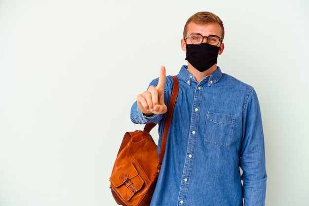 Jeune étudiant caucasien homme étudiant l'allemand isolé sur un mur blanc montrant le numéro un avec le doigt.