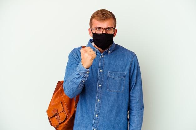 Jeune étudiant caucasien homme étudiant l'allemand isolé sur un mur blanc montrant le poing à la caméra, expression faciale agressive.
