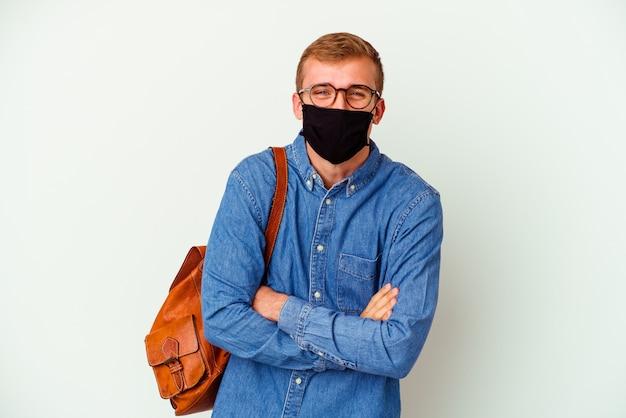 Jeune étudiant caucasien homme étudiant l'allemand isolé sur un mur blanc en riant et en s'amusant.