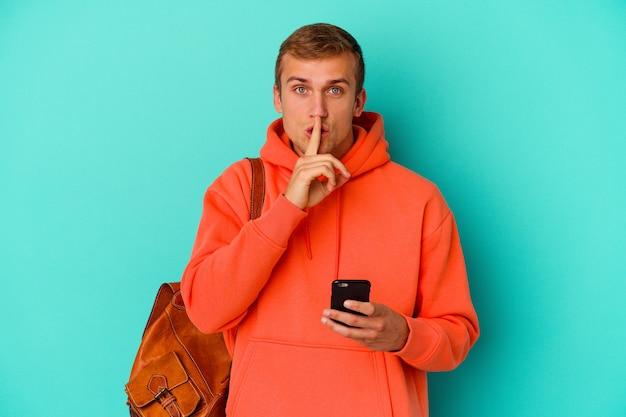 Jeune étudiant caucasien tenant un téléphone portable isolé sur bleu gardant un secret ou demandant le silence.
